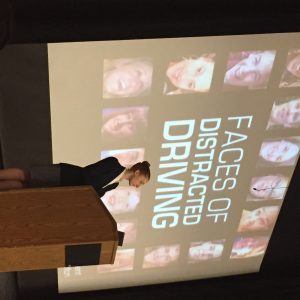 CATA board member Dana Paris at podium in front of faces of distracted driving slide of presentation.