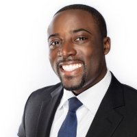 Photo of attorney Kwame Christian in a black suit and blue tie, smiling at the camera, view from chest up, on white background.